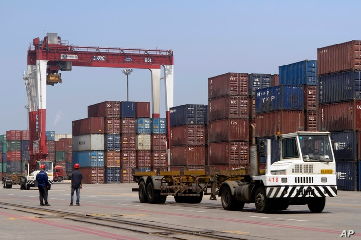 In this file photo from July 24, 2019, workers watch a truck drive past stacks of shipping containers at a port in Yingkou in…