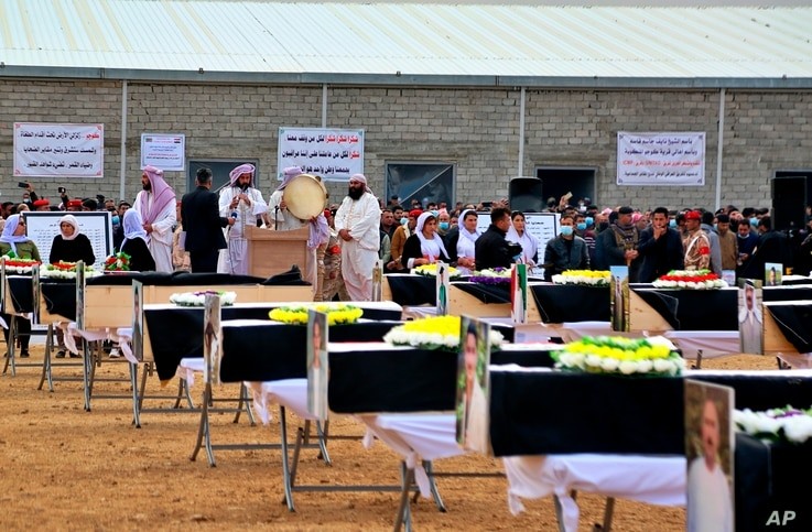 Mourners prepare to bury the remains of Yazidi victims in a cemetery in Sinjar, Iraq, Saturday, Feb. 6, 2021. 104 Yazidi killed by the Islamic State group six years ago were given a proper burial in a cemetery in Sinjar's Kocho village in the country's north.