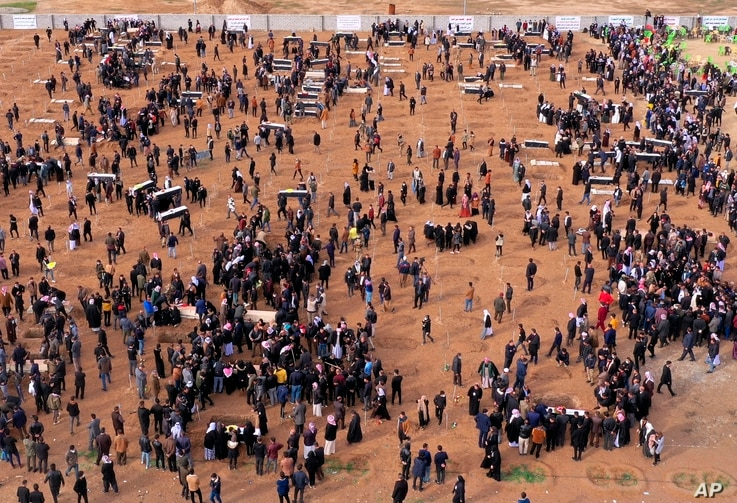 An aerial view of mourners preparing to bury the remains of Yazidi victims in a cemetery in Sinjar, Iraq, Feb. 6, 2021.