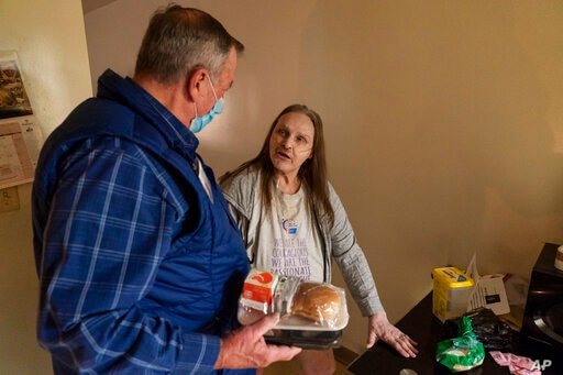 Meals on Wheels of Rhode Island driver Jim Stotler, left, delivers a meal to Rhonda Valoir, 66, at her apartment in Pawtucket, Nov. 20, 2020.