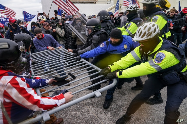 FILE - In this Jan. 6, 2021, file photo, violent insurrectionists loyal to President Donald Trump hold on to a police barrier at the Capitol in Washington.