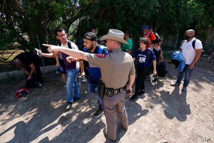 FILE - In this Wednesday, June 16, 2021 file photo, A Texas Department of Public Safety officer in Del Rio, Texas directs a...