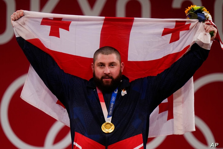 Lasha Talakhadze of Georgia holds his national flag as he celebrates the gold medal he won at the men's +109kg weightlifting…