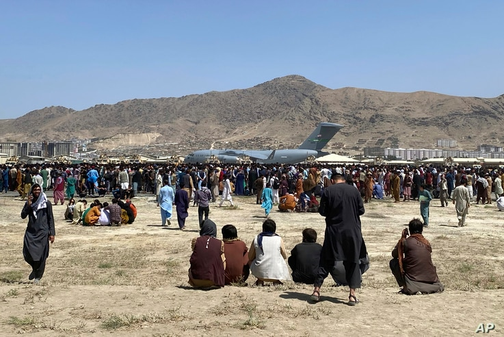 Hundreds of people gather near a U.S. Air Force C-17 transport plane at the perimeter of the international airport in Kabul,...