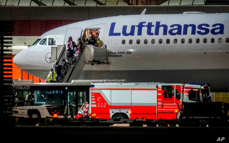FILE - In this Aug. 18, 2021, file photo, people disembark from a Lufthansa aircraft coming from Tashkent in Uzbekistan that…