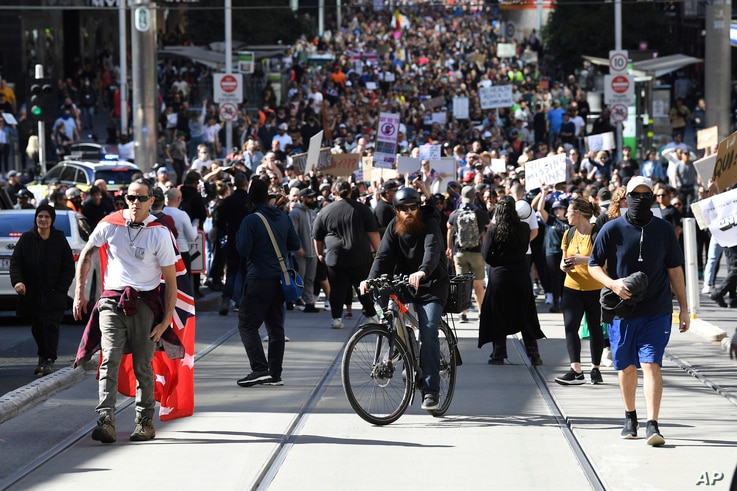 Hundreds of protesters march on a street during an anti-lockdown protest in Melbourne, Australia, Aug. 21, 2021.