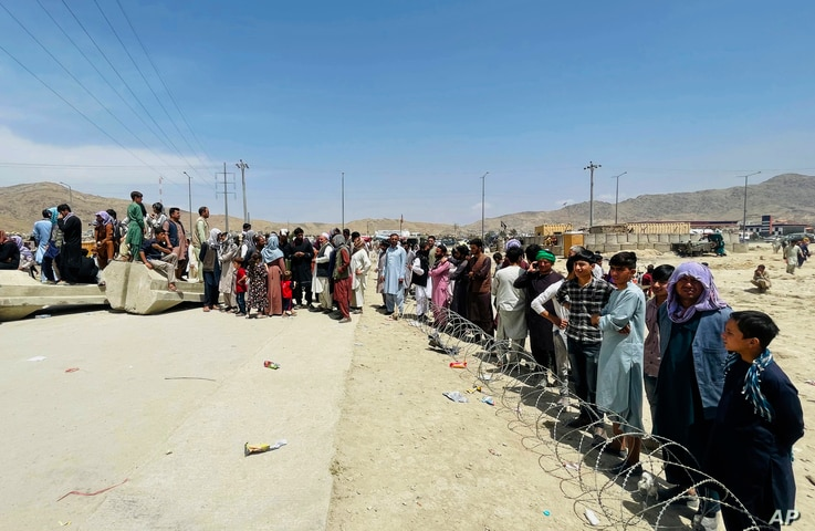 Hundreds of people gather outside the international airport in Kabul, Afghanistan, Tuesday, Aug. 17, 2021.