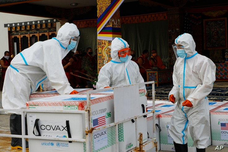 This photograph provided by UNICEF shows airport personnel in protective suit handle unloaded 500,000 doses of Moderna COVID-19 vaccine gifted from the United States arrived at Paro International Airport in Bhutan, July 12, 2021