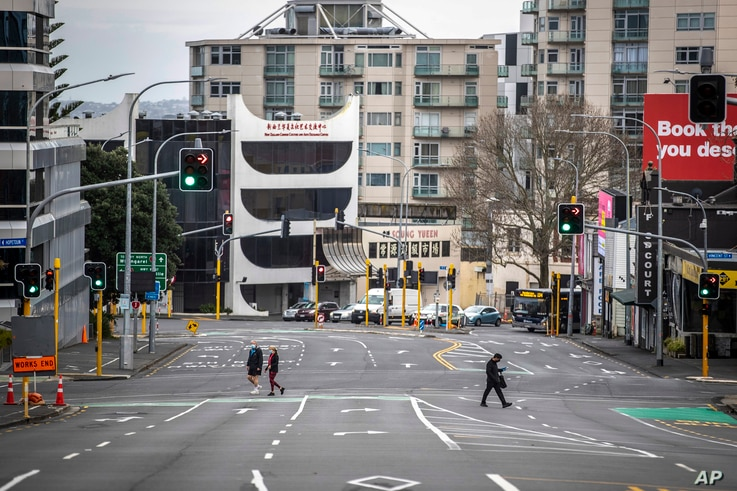 People cross nearly empty streets in the central business district of Auckland, New Zealand, Aug. 27, 2021.