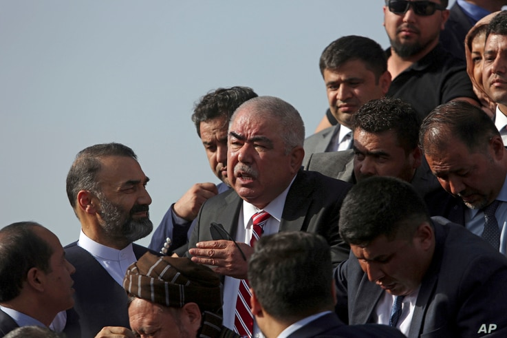 FILE - Abdul Rashid Dostum, center, a former warlord and Afghanistan's vice president at the time, disembarks with members of his entourage from his plane on arrival at Kabul International Airport, in Kabul, Afghanistan, July 22, 2018.