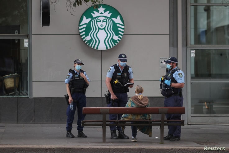 Police officers speak with a member of the public during a law enforcement operation to prevent anti-lockdown protesters from gathering during a lockdown to curb the spread of the COVID-19 in Sydney, Australia, July 31, 2021.