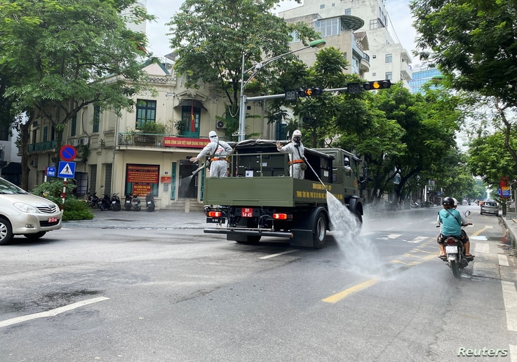 Men wearing personal protective equipment (PPE) disinfect a street as the city is under lockdown during the COVID-19 outbreak in Hanoi, Vietnam July 26, 2021.