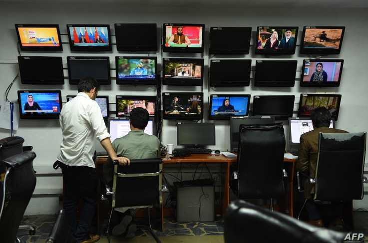 In this photo taken on September 11, 2018, Afghan reporters from Tolo News work in the newsroom of Tolo TV station in Kabul.  ...