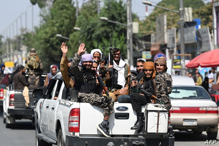 Taliban fighters wave as they patrol in a convoy along a street in Kabul on September 2, 2021. (Photo by Aamir QURESHI / AFP)