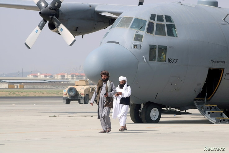 FILE PHOTO: The Taliban march in front of a military plane a day after the withdrawal of US troops from Hamid Karzai International ...
