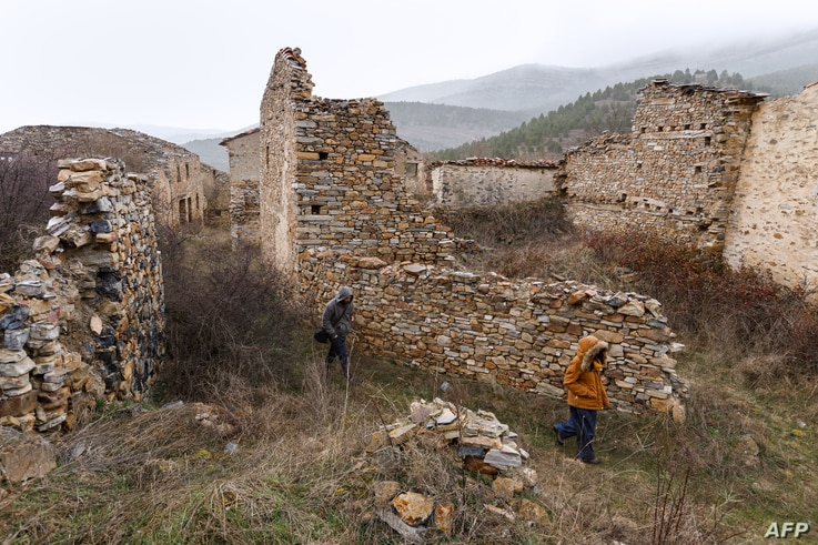 FILE - People walk in the uninhabited village of Aldealcardo, in the province of Soria, in northern Spain, February 28, 2017.