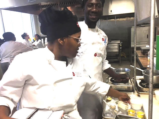 Alhaghie Dampha (right) helps prepare food for a senior meal program in Los Angeles, California. (Photo courtesy Adine Forman, HTA)