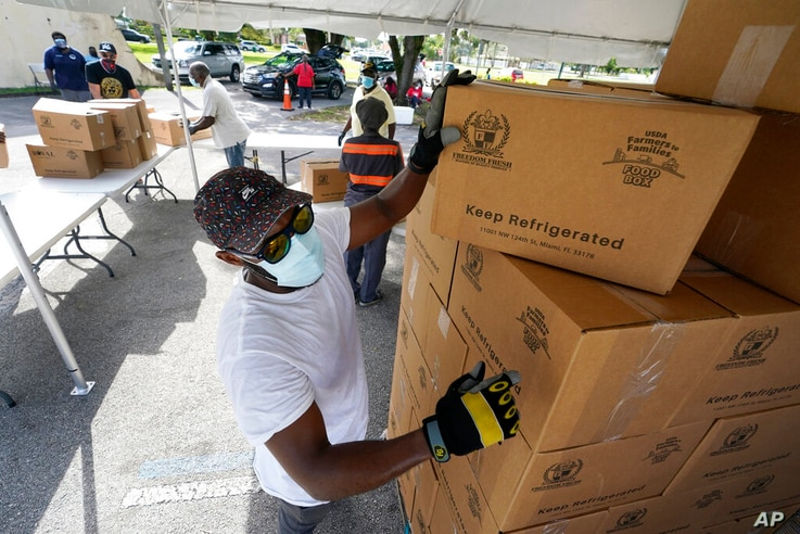 FILE - In this Oct. 6, 2020, file photo, city worker Randy Greice, foreground, unloads a pallet of food at a food distribution…