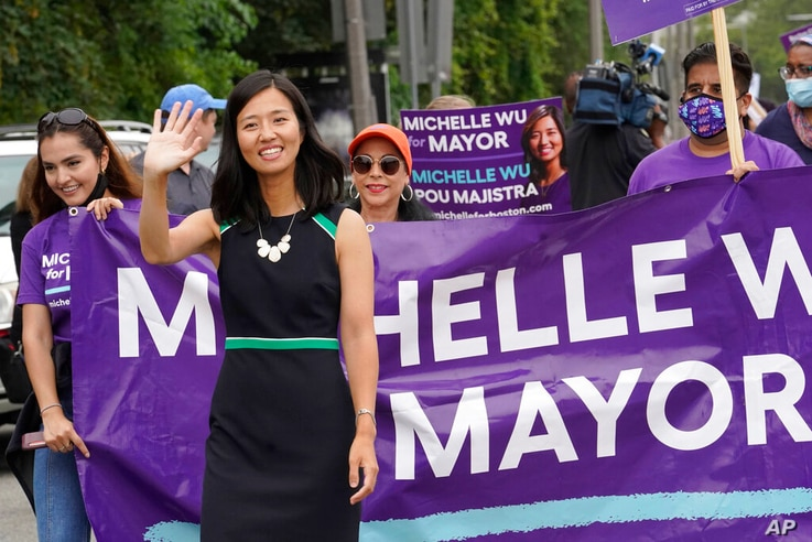 FILE- In this July 18, 2021 file photograph, Boston mayoral candidate Michelle Wu waves while walking in the Roxbury Unity...