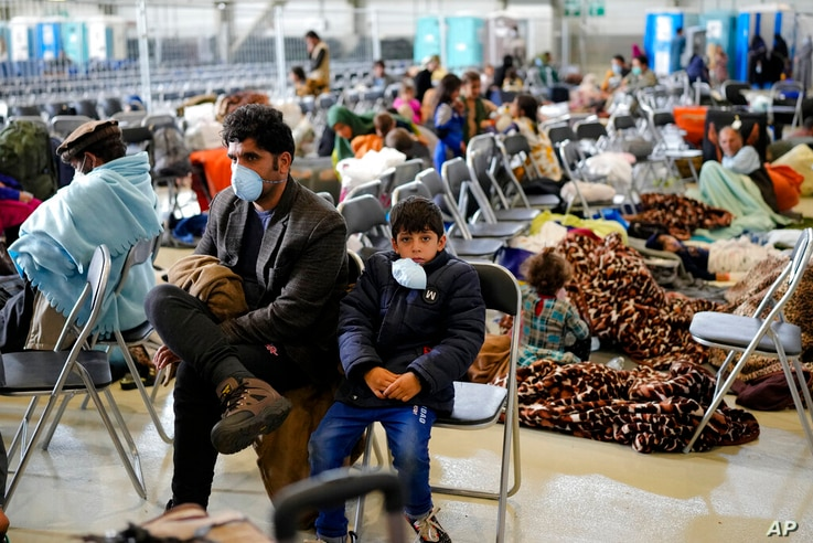 Evacuees from Afghanistan wait with other evacuees to fly to the United States or some other makeshift save location ...