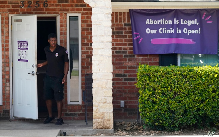 FILE - In this Sept. 1, 2021 file photo, a security guard opens the door to the Whole Women's Health Clinic in Fort Worth,…