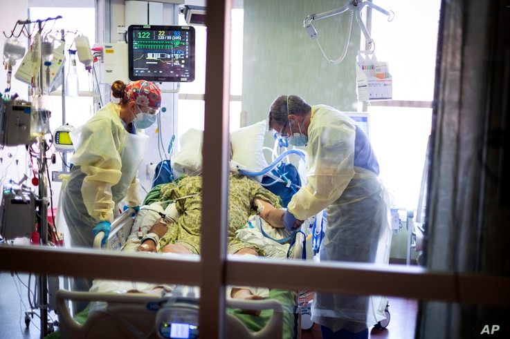 FILE - In this Aug. 31, 2021, file photo, Dr. William Dittrich M.D. looks over a COVID-19 patient in the Medical Intensive care...