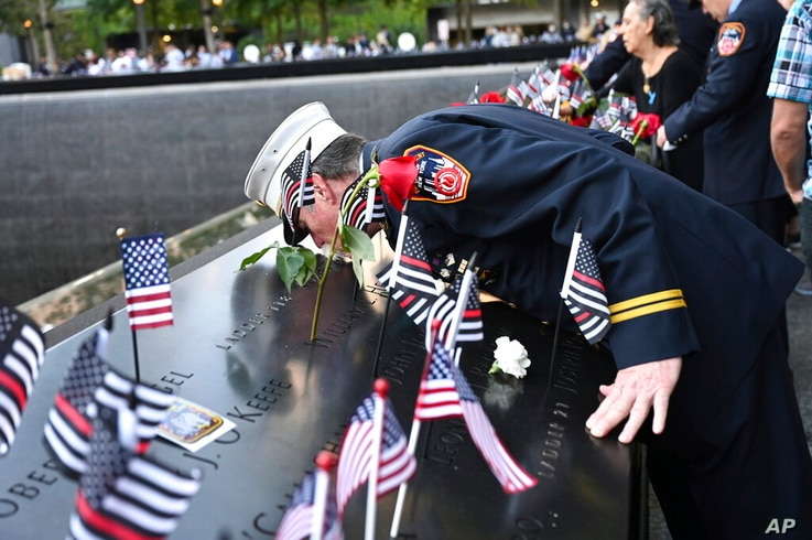 Retired Paramedic Chief Charlie Wells kisses the name of a relative killed in the attack on the World Trade Center at the…
