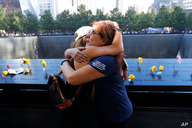 Melinda Moran and Haydee Lillo embrace after finding out they lost people who knew each other, next to the North Reflecting…