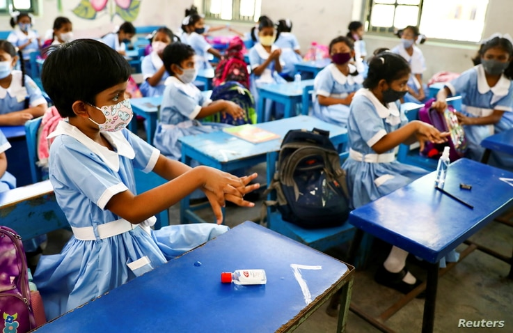 Students apply hand sanitizer in a class at the Viqarunnisa Noon School & College in Dhaka, Bangladesh, Sept. 12, 2021.