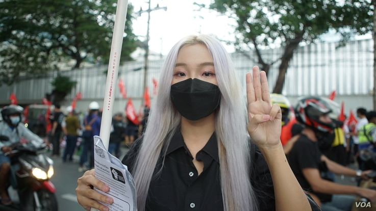Billie, a pro-democracy protester, gives the three-fingered salute, a sign of resistance borrowed from the Hunger Games trilogy.  (Vijitra Duangdee / VOA)