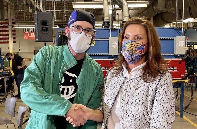 Former restaurant supervisor Brian Stauffer (left) applied for Gov. Gretchen Whitmer's (right) job training program, Futures for Frontliners, to learn how to weld, August 2021. (Photo courtesy Grand Rapids Community College)