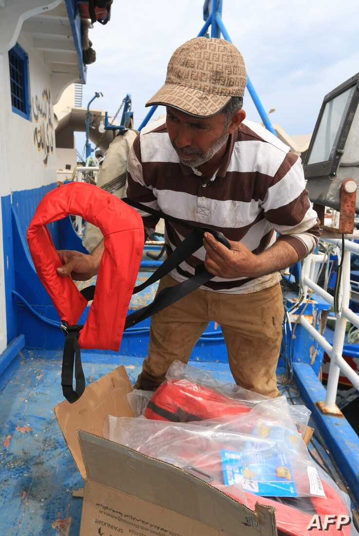 Tunisian fishermen prepare life jackets to be used in case they meet migrants in distress at sea, May 21, 2019, at the port of Zarzis, Tunisia. Most of the fishermen have already brought back migrants, saving hundreds of lives over the years.
