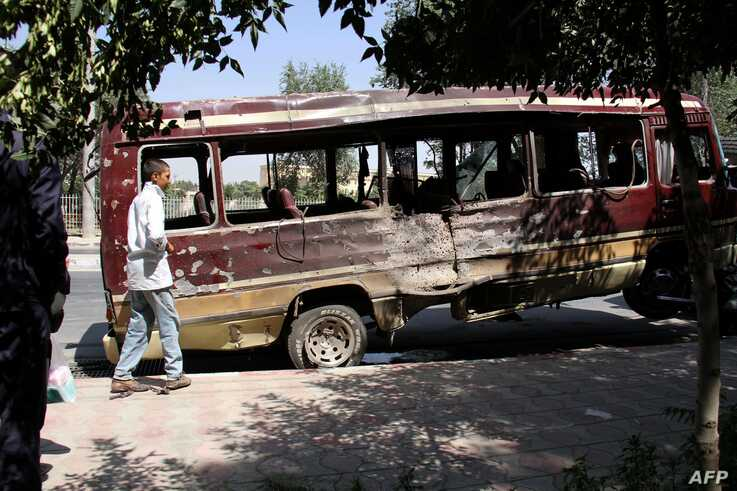 A boy walks past the wreckage of a bus following a suicide bombing in Kabul on July 25, 2019. At least 10 people -- including several women and a child -- were killed and 41 others wounded by a series of blasts that rocked the Afghan capital on July…