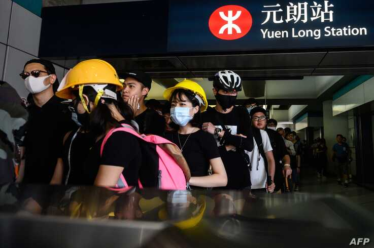 Protesters line up inside an MTR station in the Yuen Long district of Hong Kong on July 27, 2019, before an expected protest march in the afternoon. Crowds of Hong Kong protesters defied a police ban and began gathering in a town close to the Chinese border to rally against suspected triad gangs who beat up pro-democracy demonstrators there last weekend. Philip FONG / AFP