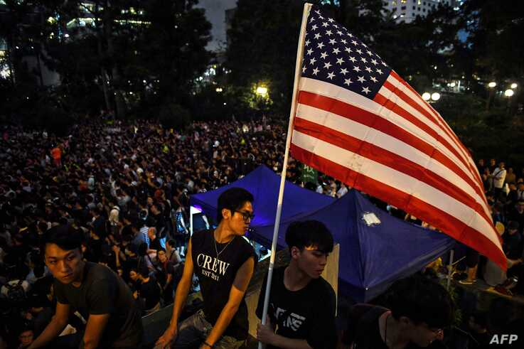 Anti-extradition bill protesters hold an American flag at a gathering at Chater House Garden in Hong Kong, Aug. 16, 2019.