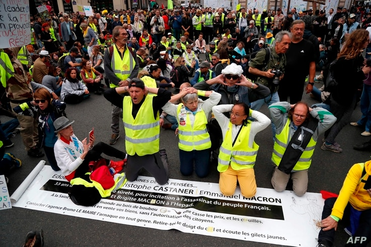 """""""Yellow vest"""" protesters kneel during an anti-government """"yellow vests"""" (gilets jaunes) protest in Paris on September 28, 2019.  / AFP / Zakaria ABDELKAFI"""