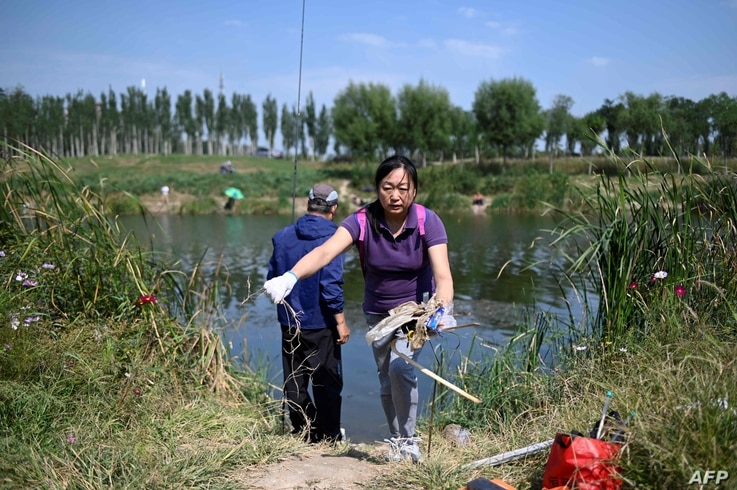A volunteer collects trash by a river during the World Cleanup Day in Beijing, on September 21, 2019. / AFP / WANG ZHAO
