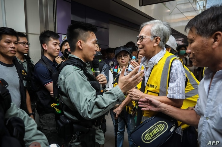 """This picture taken on September 7, 2019 shows """"Grandpa Wong"""" (centre R), 85, speaking with a riot police officer along with other """"silver hair"""" volunteers in the Tung Chung district in Hong Kong. Despite his age, Wong is a regular sight at Hong Kong…"""