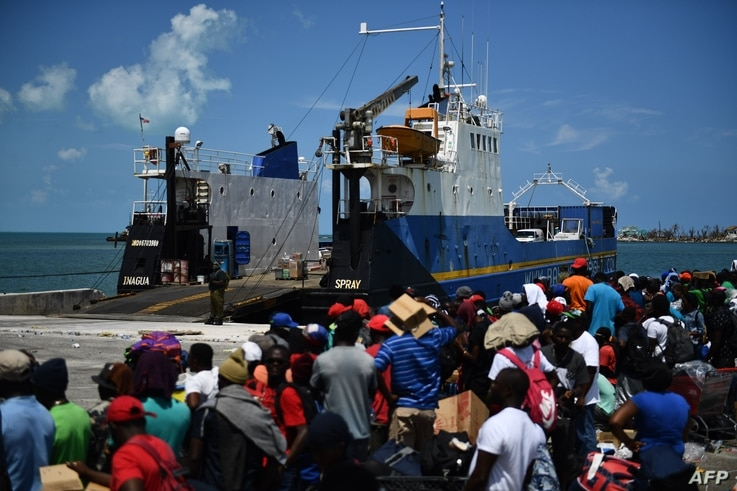 People wait to board a cargo ship for evacuation to Nassau at the port after Hurricane Dorian September 7, 2019, in Marsh Harbor, Great Abaco. Bahamians who lost everything in the devastating passage of Hurricane Dorian were scrambling Saturday to…