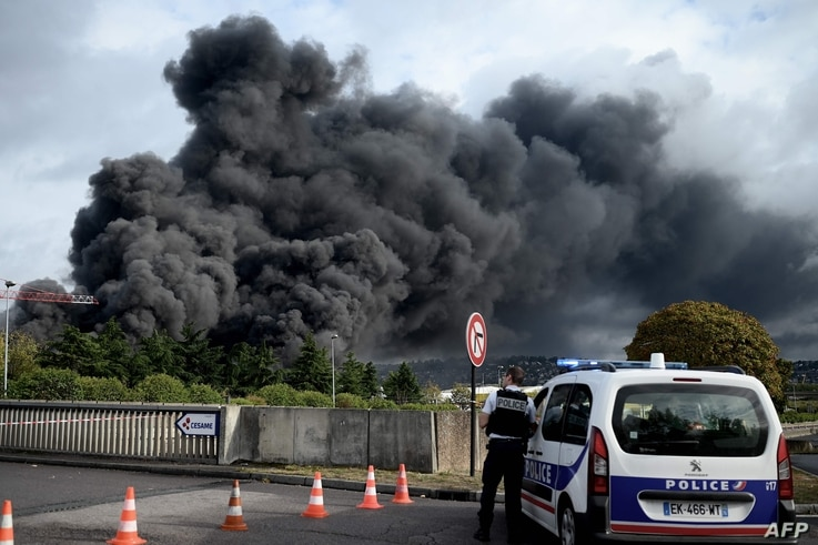 A policeman stands on a blocked road in Le Petit-Quevilly on September 26, 2019 as smoke billows from a Lubrizol factory classified Seveso high-threshold site on fire in Rouen. Residents of twelve towns including Rouen have been asked to stay at…