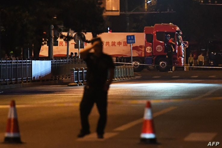 Trucks with propaganda slogans are seen on Beijing's Changan Avenue, the city's main east-west boulevarde during an overnight rehearsal of a military parade to mark Communist China's 70th anniversary, in Beijing on September 7, 2019.   The parade on…
