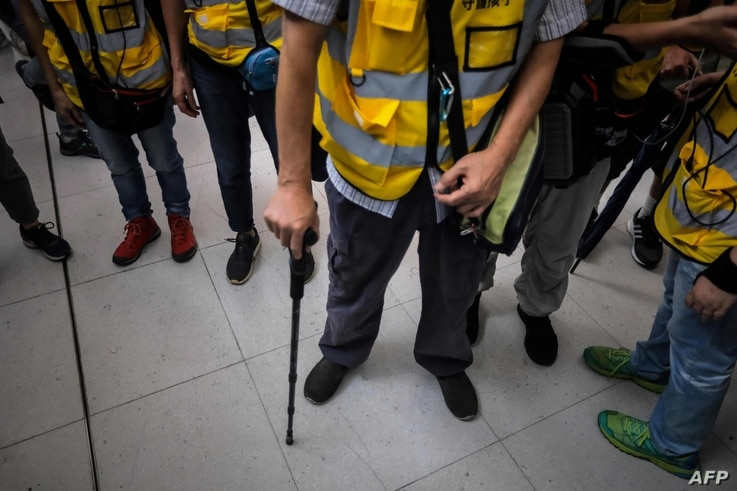 """This picture taken on September 7, 2019 shows """"Grandpa Wong"""" (C), 85, leaning on his walking stick with other """"silver hair"""" volunteers after intervening in a confrontation between protesters and riot police in the Tung Chung district in Hong Kong…"""