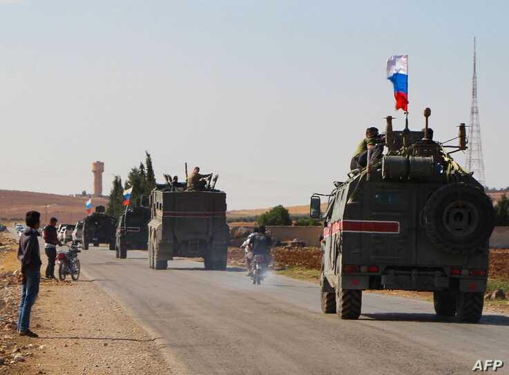 TOPSHOT - A convoy of Russian military vehicles drives toward the northeastern Syrian city of Kobane on October 23, 2019. -…