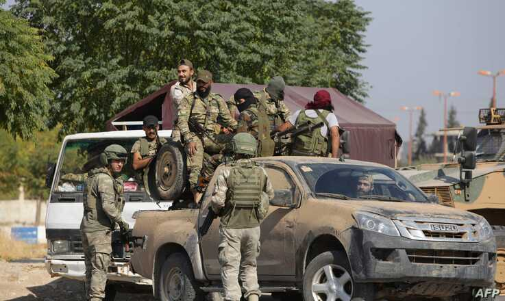 Turkish soldiers and Turkey-back Syrian fighters patrol the northern Syrian Kurdish town of Tal Abyad, on the border between…