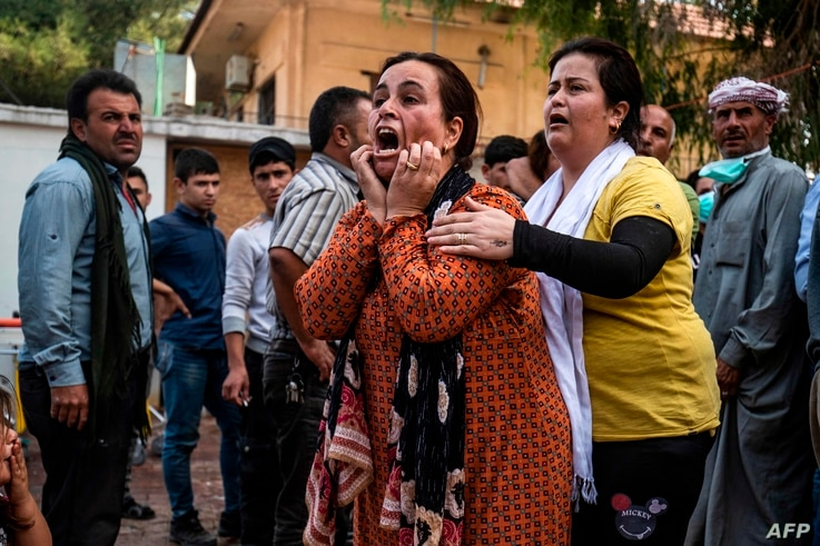 A woman reacts as the body of a man killed during Turkish shelling in the area surrounding the Syrian Kurdish town of Ras al-Ain arrives at a hospital in the nearby town of Tal Tamr, Oct. 18, 2019.