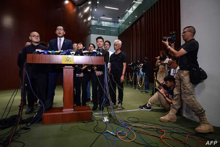 Pro-democracy lawmakers, including Democratic Party politician Lam Cheuk-ting (2nd L), hold a press conference outside the…