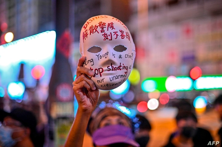 TOPSHOT - A woman holds a mask with slogans written on as protesters gather outside Mong Kok police station in Hong Kong on…
