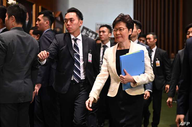 Hong Kong Chief Executive Carrie Lam (R) walks past protesting pro-democracy lawmakers (behind L) as she arrives for a question…