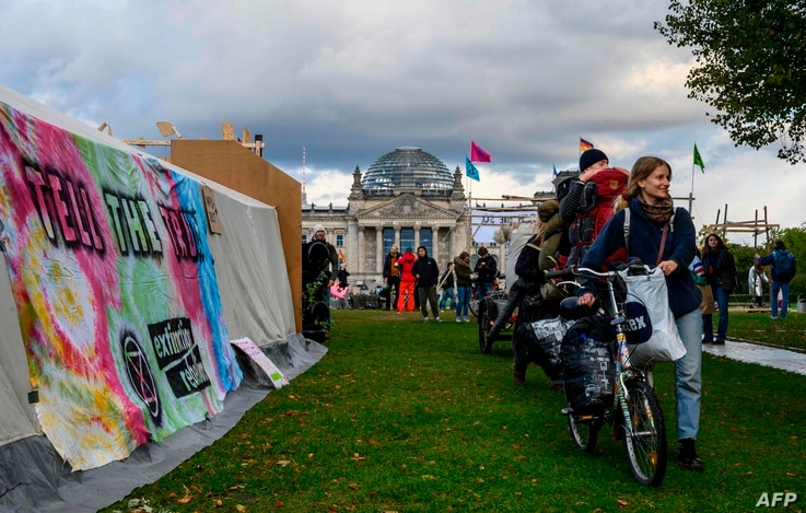 Activists arrive at a camp set up by Extinction Rebellion climate activists next to the chancellery, and the Reichstag building…
