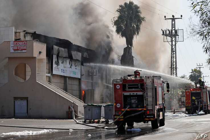 TOPSHOT - Israeli firefighter trucks douse a burning factory in the southern Israeli town of Sderot, after it was reportedly…